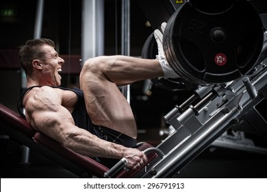 Man in gym training at leg press to define his upper leg muscles