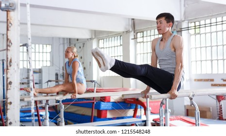 Man gymnast training gymnastic action at steel bars in gym, woman on background