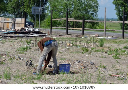 A man of Gypsy nationality is looking for metal in a dump with the help of a self-made metal detector. May 15,2018. Kiev,Ukraine