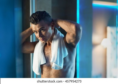 Man Hair Care Concept. Portrait Of Handsome Sexy Man With Naked Upper Body Touching His Wet Thick Hair, His Hairstyle In Bathroom