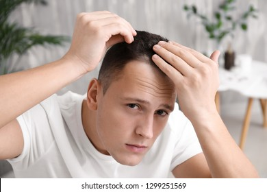 Man with hair loss problem at home