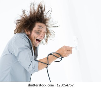 Man with hair standing on end plugging bared wire into a wall socket