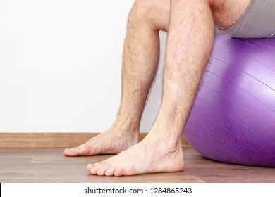 Man with hairy legs sitting on a fitness ball. Close-up.