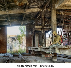 Man in half face mask, hood jacket and military pants with backpack sitting inside old ruined abandoned building. Bandit or hiding criminal or special forces. HDR panoramic image