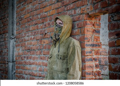Man in half mask and hood hiding from something inside abandoned building leaning on the bricks wall and peeping through the door