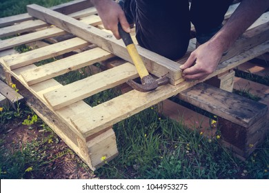 A man with a hammer building a construction out of wooden pallets. Upcycling concept