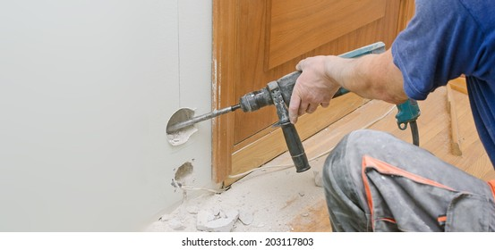 Man with Hammer drill doing hole for socket. Place for text.