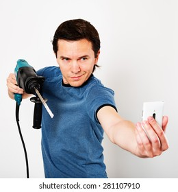 Man with hammer drill in hands. He is making selfie in time of starting of home renovation.