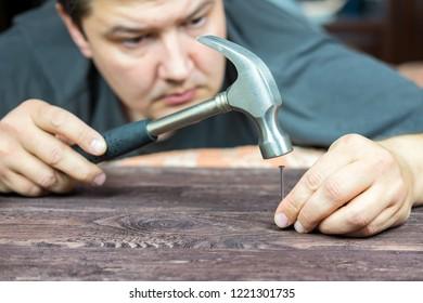 Man hammering a nail into a tree