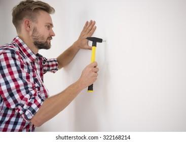 Man hammering a nail into the wall