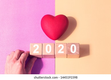 Man hand arranging wood block stacking with icon 2020 year healthcare, heart, medical, insurance for your health. Or Valentine's day holiday in 2020.