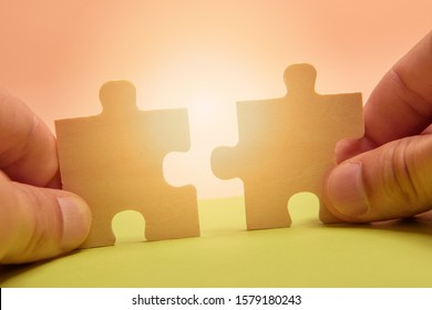 Man hand assembling puzzles on lime background.