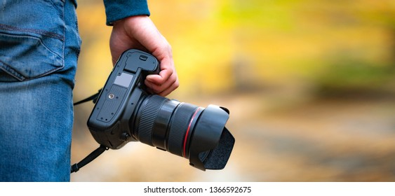 man hand with camera in autumn forest