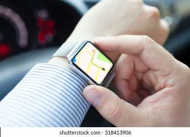 Man hand in the car with watch and app navigation on the screen