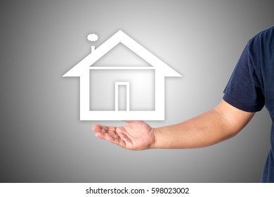 A man hand in casual wear showing a property logo isolated over gray background with copy space for add word text title.