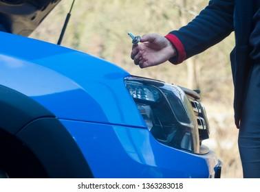 man hand changing light bulb on car headlight