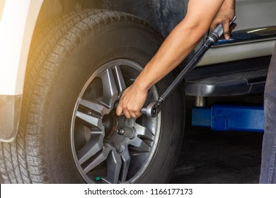 Man hand changing tire of the car by torque wrench in workshop service station.
