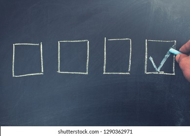 man hand with checked the box by symbol of tick on chalkboard