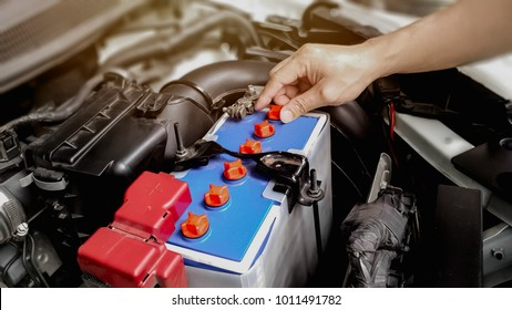Man hand checking car battery on car engine background. Selective focus.