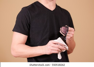 Man hand cleaning black sun glasses lens with isolated background.