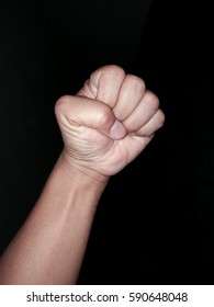 Man hand clenched fist on black background