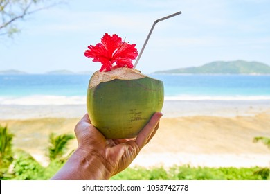 man hand with coconut cocktail in front of tropical beach, la digue, seychelles