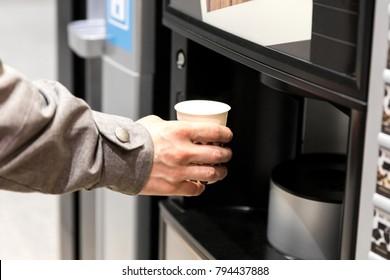 Man hand with coffee, vending coffee machine