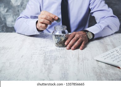Man hand coins with jar on ofice desk