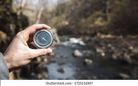 man hand compass in forest and lake background