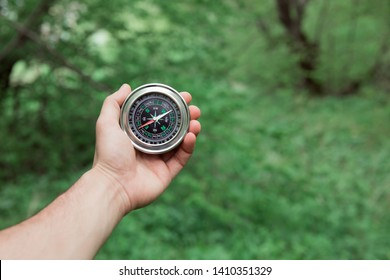 man hand compass in green  forest background
