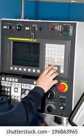 man hand  the controls of a machine CNC