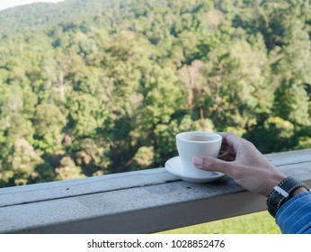 Man hand with a cup of coffee on wooden bar. Beauty nature background of mountains landscape  at Doi-Montngo , Chiang Mai, Thailand