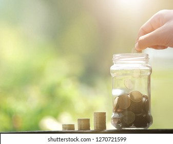 Man hand dropping coin and coins and jar. Saving money concept.