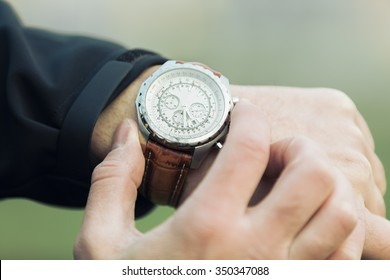 Man hand with elegant expensive watch with leather strap