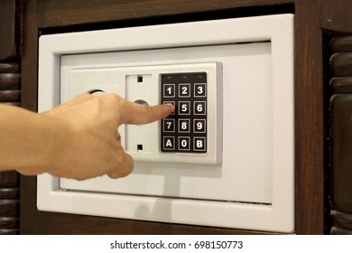 man hand entering code on keypad of mini safe box in hotel room