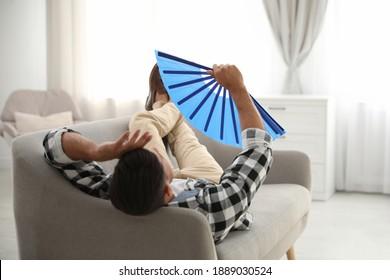 Man with hand fan lying on sofa. Summer season