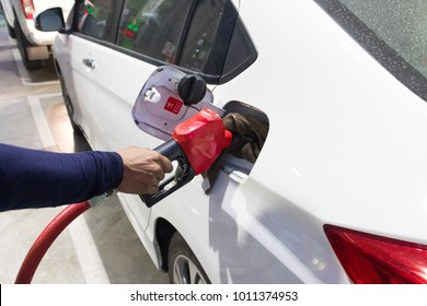 Man hand filling the petro tank in to the white car, Man hand holding the red petro handle