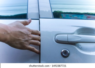 Man hand or finger pinched by the car door; close up portrait of finger pinched, slammed by the car door,  accident concept; 40s asian adult man hand or finger model
