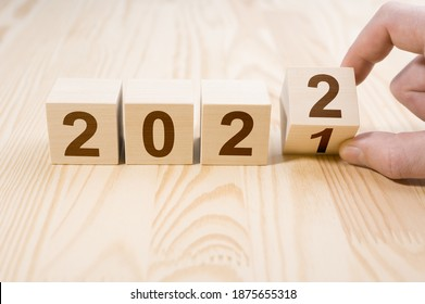 Man hand flipping cubes with year 2021 to 2022. new year concept. copy space. Hand holding wooden cube with flip over block 2021 to 2022 word on table background