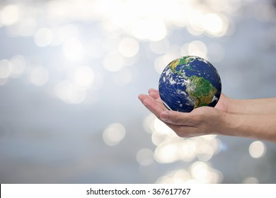 man hand gesture palm up holding world on blurred peaceful water surface background concept.Elements of this image furnished by NASA