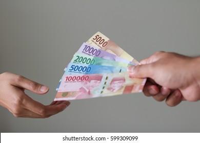 Man Hand give Indonesian Money Rupiah
