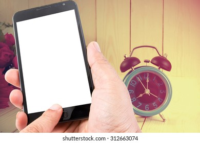 Man hand hold blank touch screen smart phone on vintage wood background and flowers with retro alarm clock.