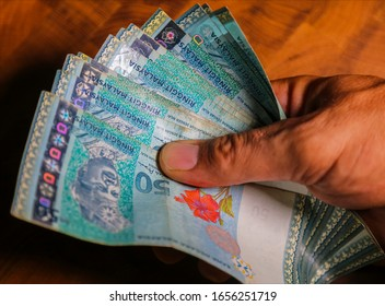 Man hand hold a bunch of  Malaysian ringgit banknote, the currency of Malaysia.  Close up Paper Money of Malaysia. 50 Ringgit or RM50 in male hand. In front the first agong or king of Malaysia