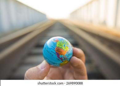 Man hand hold in hand Circle globe against metal railway in perspective road transportation against summer sunset light sky Idea symbol concept of logistic transport Future development of planet Earth