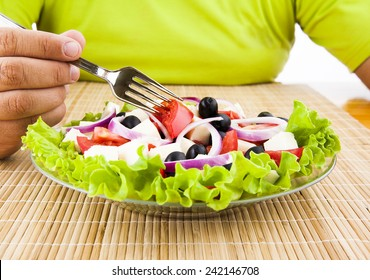 man hand hold fork with red fresh tomatoes under glass transparent plate with greek healthy salad with green leaf round onion black olive cheese Male no face unrecognizable person eating health food