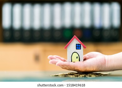Man hand hold the home model put on the gold coin with growing interest on the desk in the office, Saving money for buy house or loan for investment of real estate concept.