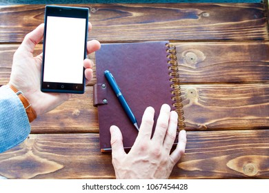 man hand hold mobil phone blank person smartphone white screen paper leather notebook on a wooden vintage table
