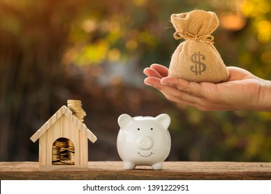 Man hand hold money bag with presenting as home and piggy bank and coin with growing interest in the public park, Saving money for buy house or loan for investment of real estate concept.