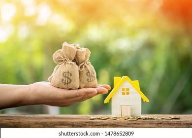 El hombre tiene una bolsa de dinero con la presentación y el modelo de casa y la moneda de oro con creciente interés en el parque público, Ahorrando dinero para comprar casa o préstamo para la inversión de negocios del plan de concepto de bienes raíces.