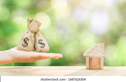 Man hand hold money bag with presenting and home model and gold coin with growing interest in the public park, Saving money for buy house or loan for plan business investment of real estate concept.